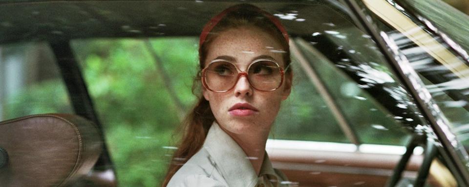 Die Dame im Auto mit Sonnenbrille und Gewehr